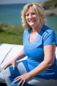 fitness instructor smiling sat on a hospital bed overlooking the sea
