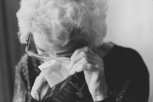 Elderly lady wiping her eyes