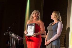 Helen receiving her award in a red dress