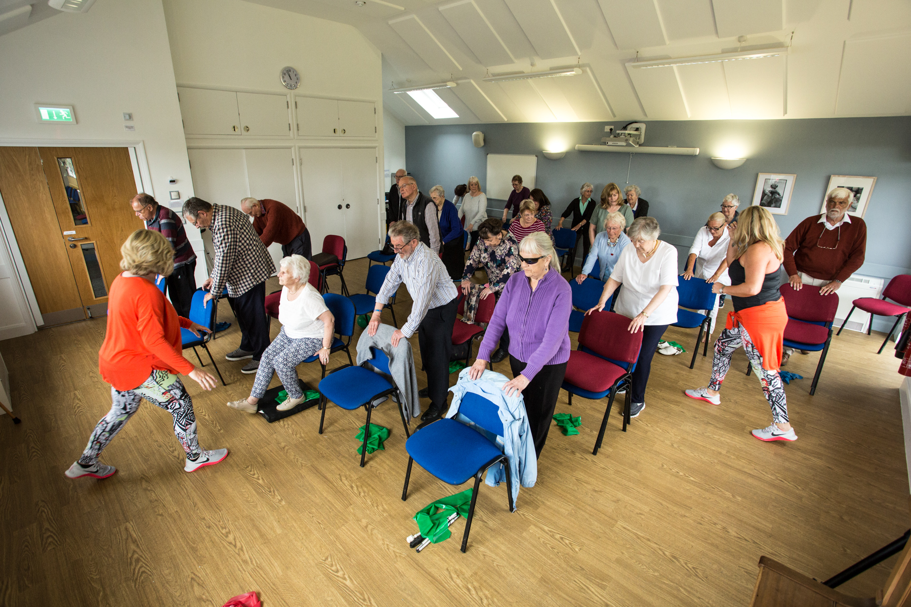 Exercise class with eldery clients smiling and standing in a classroom
